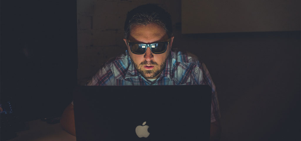 A suspicious man wearing sunglasses working on his computer